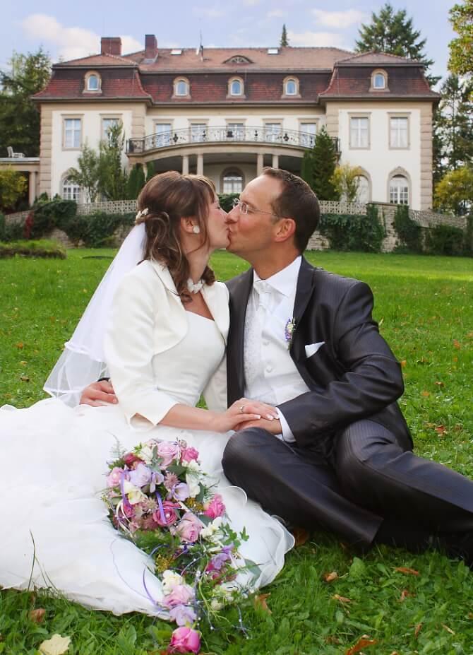 Verliebtes Brautpaar vor der Villa
